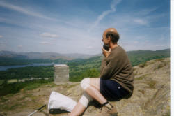 picture of a walker listening to a commentary on the view from the top of a fell using a recorded tape